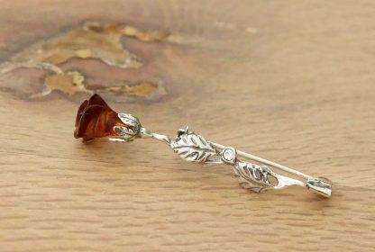 Elegantná jantárová brošňa zo striebra a pravého jantáru koňakovej farby predstavujúca rozvíjajúci sa puk ruže